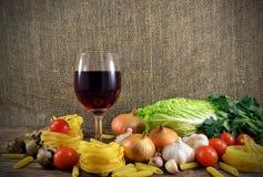 Pastas y vidrio de vino en la tabla Imagen de archivo