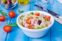 Pastasallad med tonfisk, oliv, körsbärsröda tomater och arugula arkivbilder