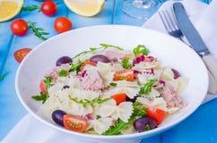 Pastasallad med tonfisk, oliv, körsbärsröda tomater och arugula arkivfoto