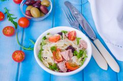 Pastasallad med tonfisk, oliv, körsbärsröda tomater och arugula arkivbild