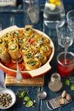 Pastasniglar som göras med lasagne och stoppas med spenat- och fetaost arkivbilder