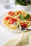 Pastaspagetti med tomatsås och ostparmesan tjänade som på den mörka plattan på tabellbakgrund arkivfoto