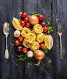 Pastatagliatelle med tomater, grönsaker och kryddor för tomatsås, sked och gaffel Royaltyfri Bild