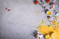 Paste crude con la cottura degli ingredienti sul controsoffitto grigio Vista da sopra, spazio della copia immagini stock