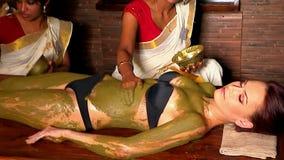 Paste de vrouwen Indische schoonheidsspecialist therapeutische klei van natuurlijk op het lichaam van de patiënt toe stock videobeelden