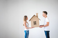 Pasteboard house. Happy couple with cardboard house Stock Images