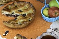 Pastei, een plak van appeltaart met kers en okkernoten, een kop thee, appelen in een mand, okkernoten en koekjes op de lijst royalty-vrije stock afbeeldingen