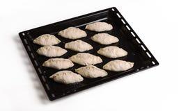 Pastei klaar voor baksel die op een zwart blad van het staalbaksel liggen Drie - kwartenmening van hierboven Royalty-vrije Stock Foto