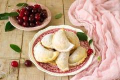 Pastei met kersen, met gepoederde suiker en bessen van verse kersen op een houten oppervlakte worden bestrooid die Royalty-vrije Stock Foto's