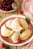 Pastei met kersen, met gepoederde suiker en bessen van verse kersen op een houten oppervlakte worden bestrooid die Royalty-vrije Stock Fotografie