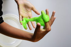 Pasteislijm elastisch en kleverig op kind` s hand stock foto