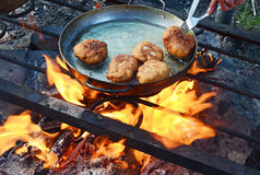Pasteitjes in een grote pan over een kampvuur in het marcheren voorwaarden worden gebraden die Stock Foto's
