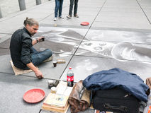Pastel artist draws Charlie Chaplin on concrete plaza at Beaubourg, Paris. Artist sits on plaza drawing huge greyscale portrait of Charlie Chaplin. Red tip Royalty Free Stock Images