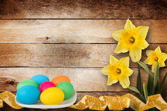 Pastel background with multicolored eggs and narcissus Stock Photos