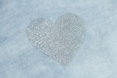 Silver heart on a blue background of cotton fabric. Romantic pas. Pastel background. Silver heart on a blue background of cotton fabric. Romantic pastel Royalty Free Stock Photography