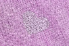 Silver heart on a pink background of cotton fabric. Romantic pastel background. Design with copy space royalty free stock photo