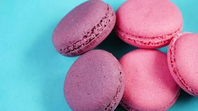 Pastel background for the theme of food. Pink cookies or macaroons lying on a blue background.