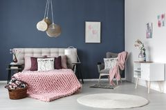 Pastel bedroom with designed lamp. Grey armchair with pink blanket and white pillow in the corner of pastel bedroom with designed lamp stock photo