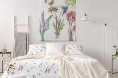 A pastel bedroom interior with a bed dressed in green plants pattern white linen. Fabric painted in flowers and birds on the backg. Round wall. Real photo stock photos