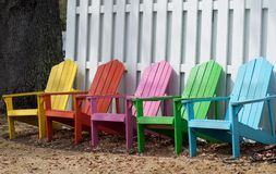 Pastel Chairs. A line of pastel colored chairs along a white picket fence Royalty Free Stock Image
