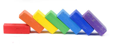 Pastel chalk. Colorful pastel chalks lined up like fallen dominoes.  Isolated against a white background Royalty Free Stock Photography
