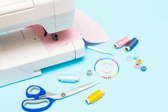Pastel color background, Dressmaker and designer desk, Handcraft accessories. Threads roll, scissors and pins.  royalty free stock image