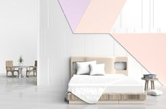Pastel color bed room. Is  are decorated with big bed, wood chair, tree in glass vase, white pillows, Blue book, white and orange cement wall it is grid pattern Stock Photos