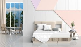 Pastel color bed room. Is decorated with  bed, wood chair, tree in glass vase, white pillows, Blue book, white and orange cement wall it is grid pattern,window Stock Photos