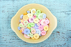 Pastel color buttons in a yellow bowl royalty free stock photography