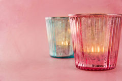 Pastel color candles on pink textured background Stock Photography