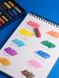 Pastel color chart. Hand-drawn on a sketchbook, over a blue background royalty free stock photography