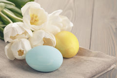 Pastel color easter eggs with tulips on table Stock Photos