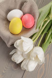 Pastel color easter eggs with tulips on table Royalty Free Stock Photos