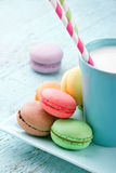 Pastel color macaroons and a cup of milk Royalty Free Stock Images