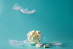 Pastel color marshmallow in glass, fly plummet. lightness Royalty Free Stock Photography