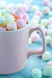 Pastel color marshmallows in a pink cup stock photography