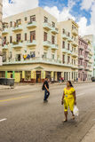 Pastel colored apartment buildings Havana. Pastel colored apartment buildings and people on the street in Central Havana, Cuba Stock Photo