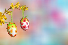 Pastel colored background, branch with group of easter eggs Stock Images