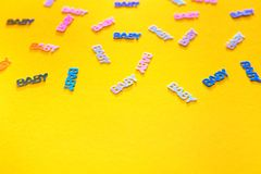 Pastel colored confetti baby on yellow background. Pastel colored confetti with words baby scattered on yellow background with copy space. Gender neutral modern stock photos