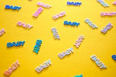 Pastel colored confetti baby on yellow background. Pastel colored confetti with words baby scattered on yellow background. Gender neutral modern trendy baby stock photos