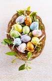 Pastel colored decor Easter eggs in a woven plate Stock Image
