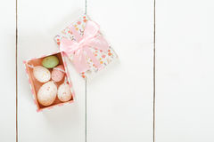 Pastel colored easter eggs in a gift box over white wooden background. Stock Photos