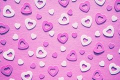 Pastel colored heart confetti on pink background. Pastel colored heart confetti scattered on pink background. Modern trendy flat lay design background for royalty free stock photos