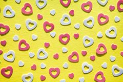 Pastel colored heart confetti on yeloow background. Pastel colored heart confetti scattered on yellow background. Modern trendy flat lay design background for stock photo