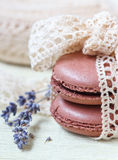 Pastel colored macaroon with vintage lace ribbon bow and lavender on light background. Close-up Stock Image