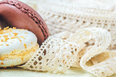 Pastel colored macaroon with vintage lace ribbon on light background Royalty Free Stock Images