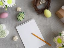 Easter holiday decorated eggs, blank paper notepad on grey background royalty free stock images