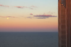 Modern tower oceanfront by full moon at dusk Stock Photos