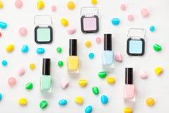 Pastel colors nail polish and eye shadows. Beauty blogger concept. Nail polish of various pastel colors, eye shadows and colorful candies. Mockup or Beauty stock photos