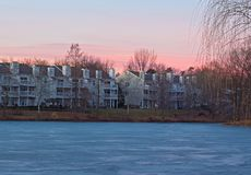 Colorful sunset in residential neighborhood near lake covered in ice. Royalty Free Stock Photo